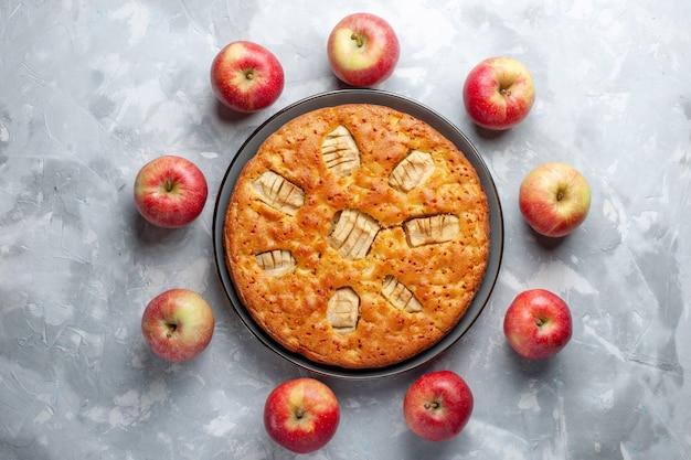 Vista de cima maçãs vermelhas frescas formando um círculo com torta de maçã no fundo branco frutas frescas maduras vitamina