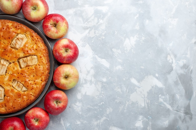 Vista de cima, maçãs vermelhas frescas, formando um círculo com torta de maçã no fundo claro frutas frescas maduras vitamina