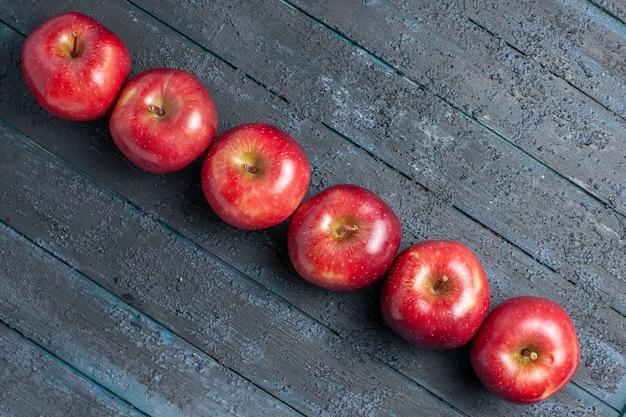 Vista de cima, maçãs vermelhas frescas, frutas maduras e maduras alinhadas na mesa azul escura, muitas frutas, cor vermelha, árvore, planta fresca