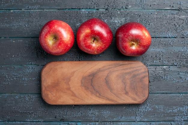 Vista de cima, maçãs vermelhas frescas, frutas maduras e maduras em azul-escuro planta de mesa cor de frutas vermelho vitamina fresco