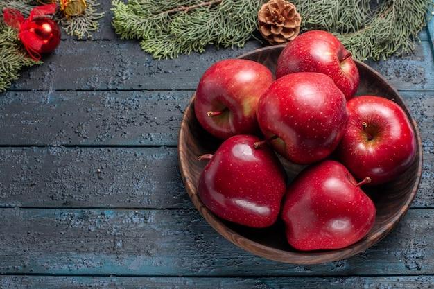 Vista de cima, maçãs vermelhas frescas, frutas maduras e maduras em uma mesa azul-escura planta muitas frutas árvore vermelha