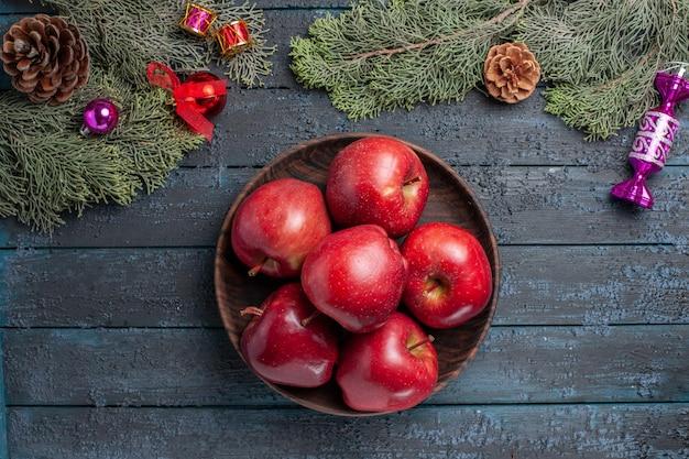 Vista de cima, maçãs vermelhas frescas, frutas maduras e maduras na mesa azul-escura, muitas frutas vitamina árvore vermelha fresca