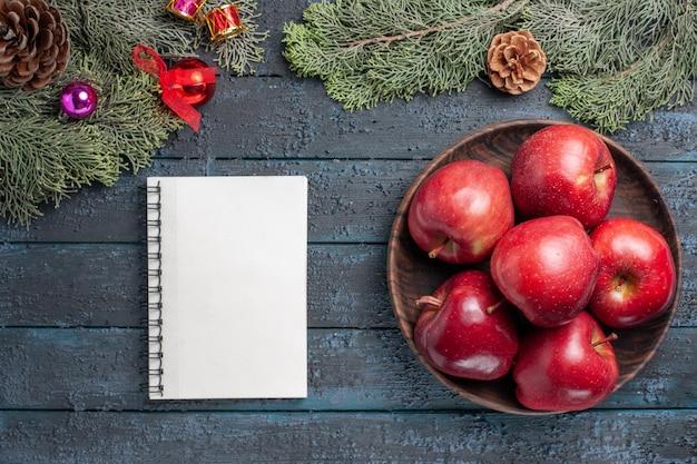 Vista de cima, maçãs vermelhas frescas, frutas maduras e maduras na mesa azul-escuro, muitas árvores frutíferas cor vermelho fresco