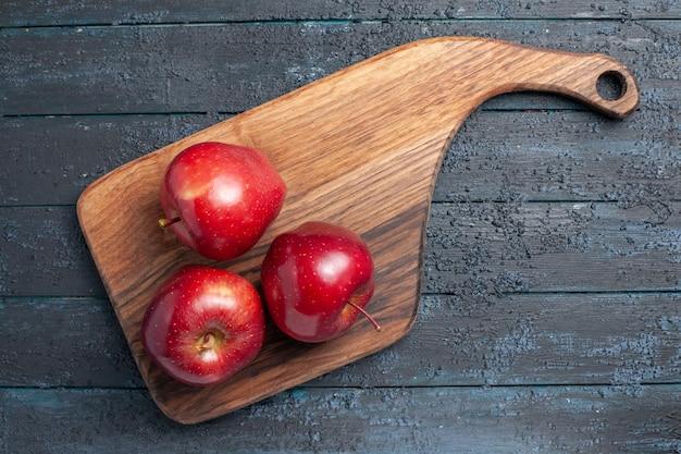 Vista de cima, maçãs vermelhas frescas, frutas maduras e maduras na mesa azul escuro.