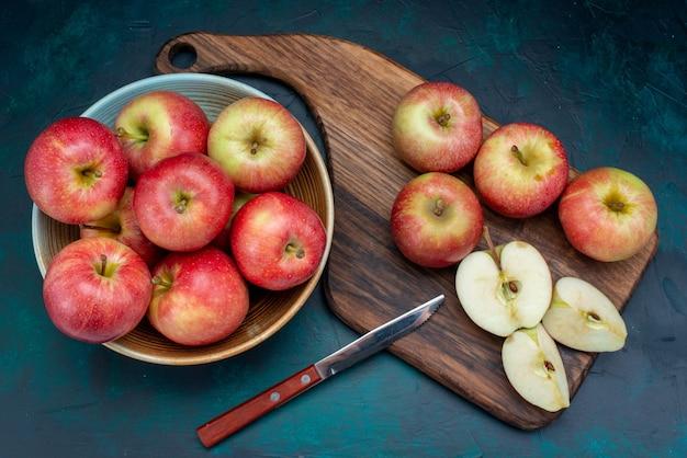 Vista de cima maçãs vermelhas frescas suculentas e maduras dentro do prato na superfície azul escura frutas maduras frescas
