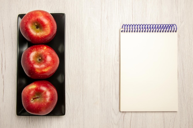 Vista de cima maçãs vermelhas maduras frutas frescas dentro de uma panela preta sobre mesa branca frutas maduras cor vermelha fresca
