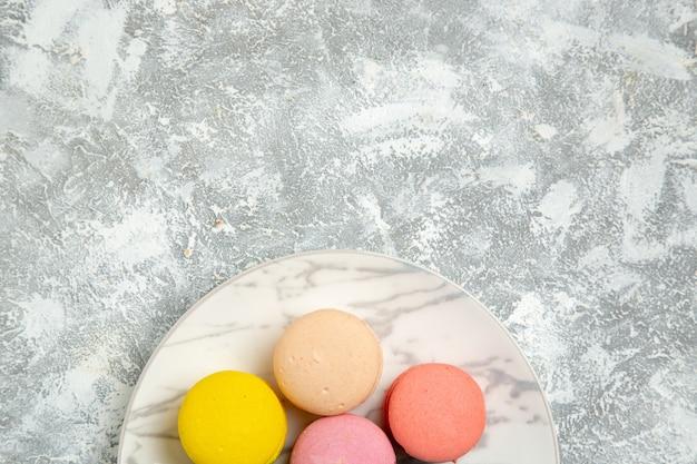 Vista de cima mais de perto macarons franceses deliciosos bolos coloridos na superfície branca bolo biscoito açúcar biscoito torta doce
