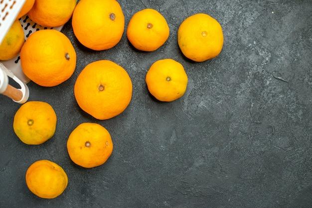Vista de cima, mandarinas e laranjas espalhadas da cesta de plástico na superfície escura