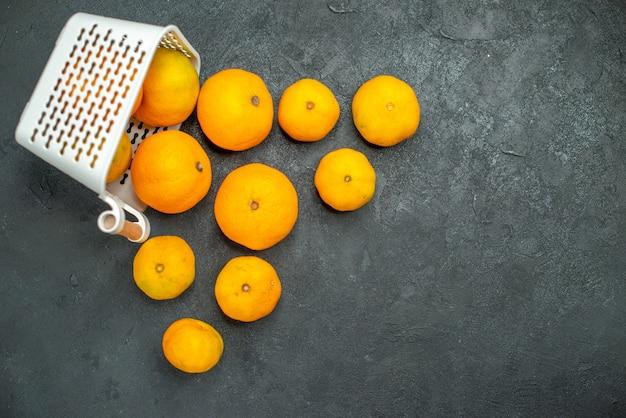 Vista de cima, mandarinas e laranjas espalhadas de uma cesta de plástico em fundo escuro