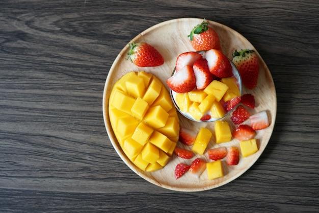 Vista de cima manga madura fresca e fruta morango em um copo com biscoitos de iogurte de soja em um prato de madeira