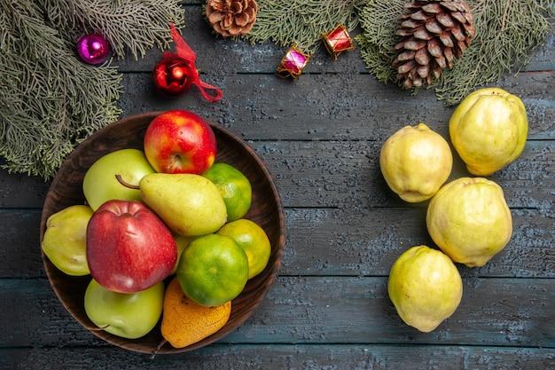 Vista de cima marmelos maduros com frutas frescas em uma mesa rústica azul-escura com muitas plantas frescas e árvores frutíferas maduras