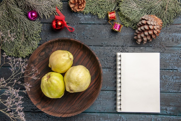 Vista de cima marmelos maduros frescos frutas ácidas dentro do prato na mesa rústica azul-escura planta fresca frutas maduras