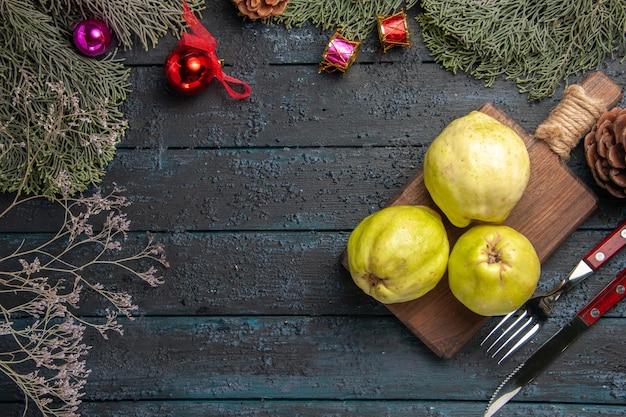 Vista de cima marmelos maduros frescos frutas ácidas em mesa rústica azul escura muitas plantas frescas árvore de frutas maduras