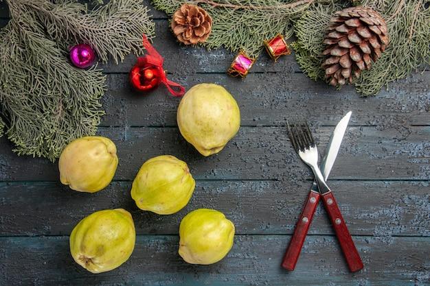 Vista de cima marmelos maduros frutas frescas em mesa rústica azul escura muitas plantas frescas árvore de frutas maduras