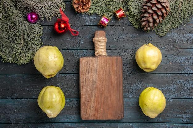 Vista de cima marmelos maduros frutas frescas em uma mesa rústica azul-escura muitas plantas frescas árvore de frutas maduras