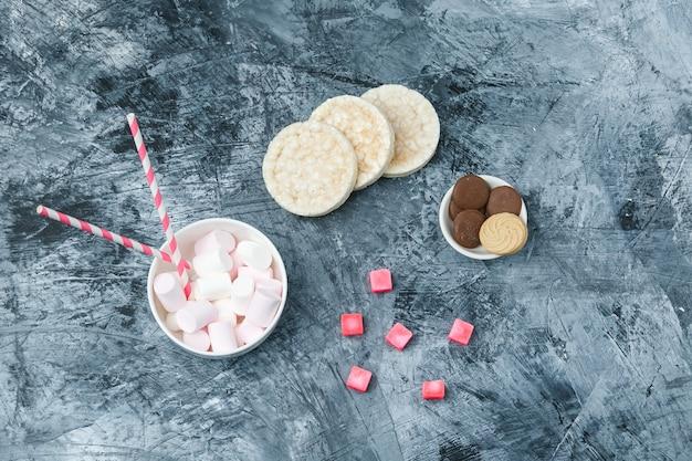 Vista de cima, marshmallows e canas de açúcar na xícara com bolachas de arroz, biscoitos e doces na superfície de mármore azul escuro. horizontal