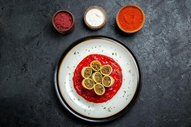 Vista de cima massa com carne fatiada com molho de tomate e temperos no espaço cinza