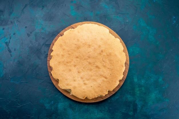 Vista de cima massa de bolo simples assada redonda formada na superfície azul escura