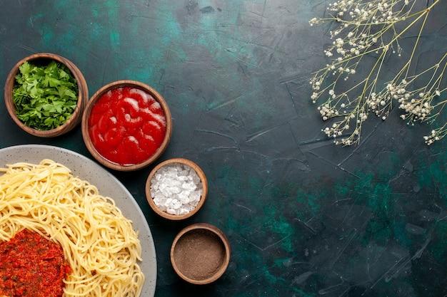 Vista de cima massa italiana cozida com carne e temperos diferentes na superfície azul escura