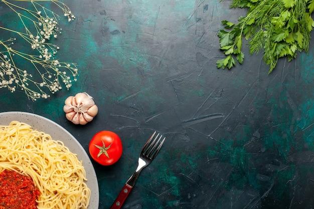Vista de cima massa italiana cozida com molho de tomate, carne picada e verduras na superfície azul