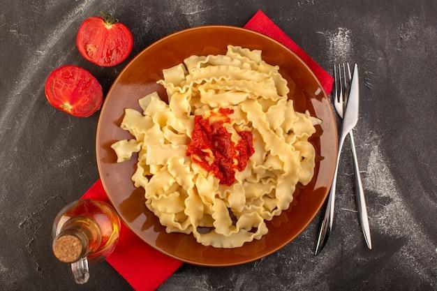 Vista de cima massa italiana cozida com molho de tomate dentro do prato com talheres e tomates