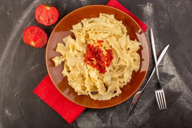 Vista de cima massa italiana cozida com talheres de molho de tomate e tomates dentro do prato