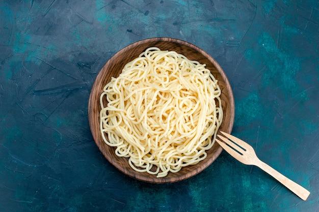 Vista de cima massa italiana cozida dentro de placa de madeira redonda sobre fundo azul.