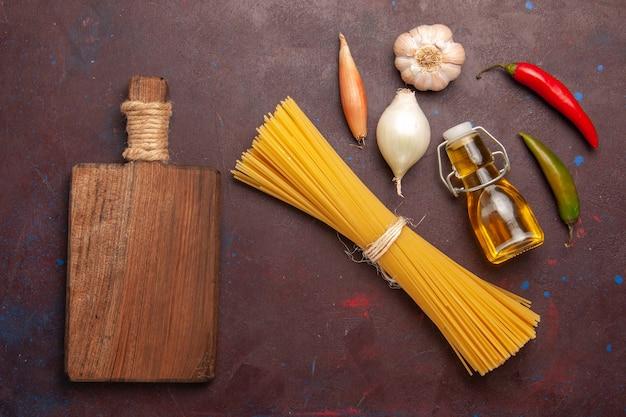 Vista de cima massa italiana crua formada há muito tempo em fundo roxo-escuro refeição massa comida massa vegetal cru