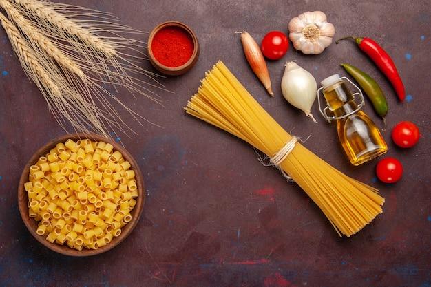 Vista de cima massa italiana crua formada há muito tempo em púrpura-escuro mesa refeição massa comida massa vegetal cru