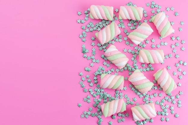 Vista de cima mastigando marshmallows coloridos junto com balas verdes em forma de estrela, tudo em uma mesa rosa, doce de açúcar