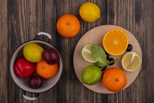 Vista de cima metades de limão com metade laranja em um suporte com limão, ameixa, ameixa cereja e pêssego em uma panela com fundo de madeira