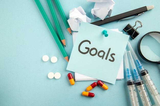 Vista de cima metas anotadas com injeções de pílulas e lápis sobre fundo azul pandêmico hospital lab vírus pílula saúde covid ciência cor