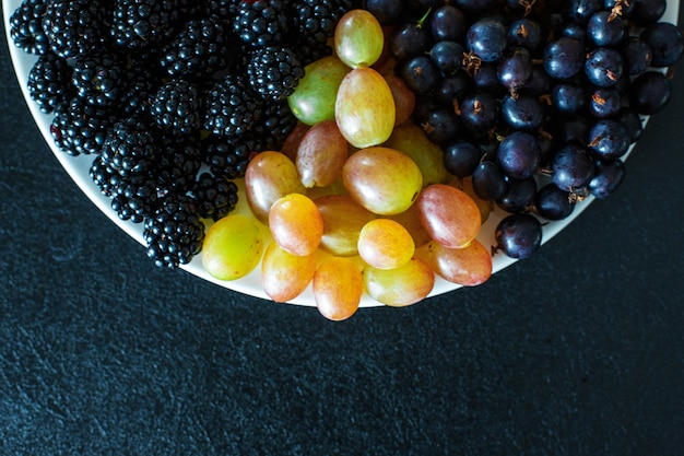 Vista de cima. mistura de frutas em um terrel branco. separação de triângulo. mistura de verão de frutas. layout elegante de bagas