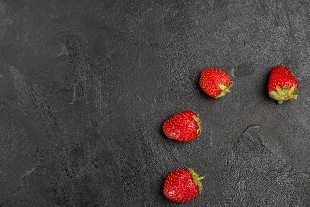 Vista de cima, morangos vermelhos frescos alinhados na mesa de cor escura, frutas vermelhas maduras