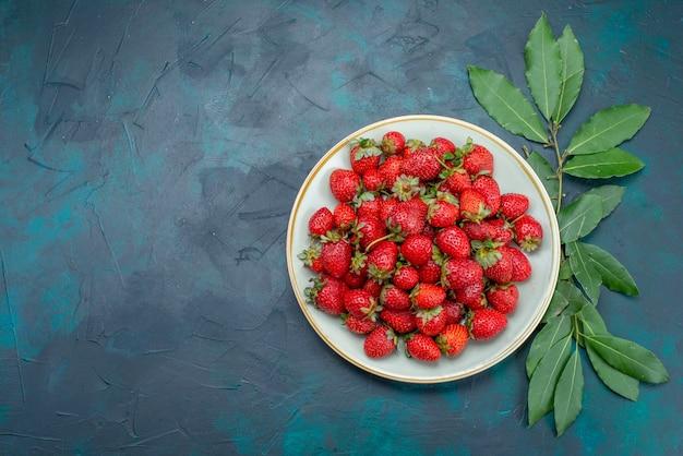 Vista de cima, morangos vermelhos frescos, frutas maduras, frutas vermelhas, dentro do prato, na mesa azul-escuro