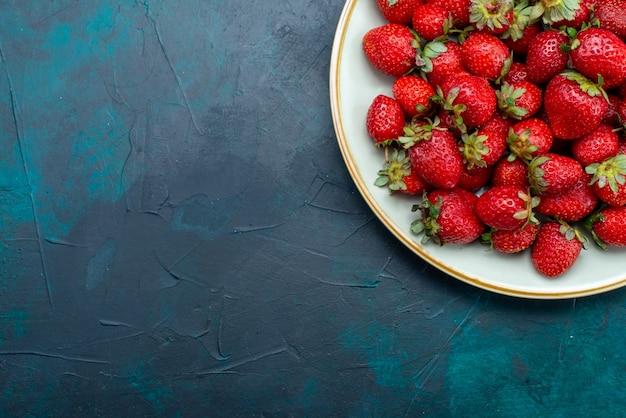 Vista de cima, morangos vermelhos frescos, frutas suaves, bagas, frutos silvestres no interior do prato na mesa azul-escuro
