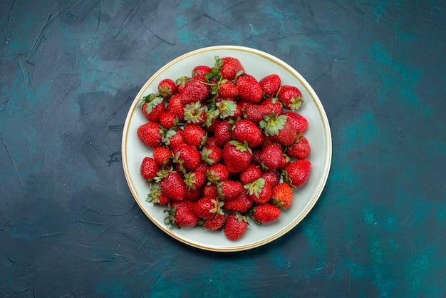 Vista de cima, morangos vermelhos frescos, frutas suaves, frutas vermelhas, dentro da placa, no fundo azul escuro.