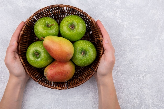 Vista de cima, mulher segurando peras com maçãs verdes em uma cesta no fundo branco