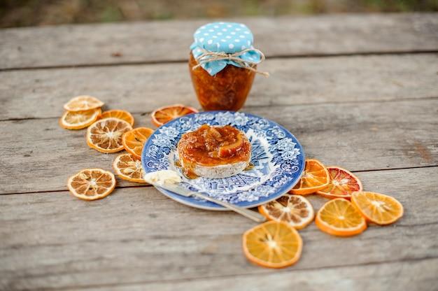 Vista de cima na composição da deliciosa geléia de laranja no pão servido no prato azul ornamentado perto da jarra de vidro e laranjas secas na mesa de madeira