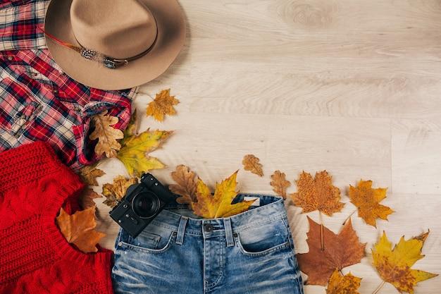 Vista de cima na horizontalidade de estilo feminino e acessórios, suéter de malha vermelho, camisa de flanela quadriculada, jeans, chapéu, tendência da moda outono, câmera fotográfica vintage, roupa de viajante