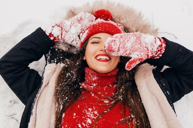 Vista de cima na jovem mulher feliz e sorridente, muito sincera, com luvas vermelhas e chapéu de malha, vestindo um casaco preto deitado na neve no parque, roupas quentes, se divertindo