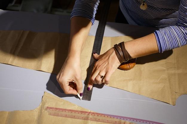 Vista de cima na mão de uma costureira com uma régua. mede a linha de corte dos espaços em branco do tecido e desenha sabão.