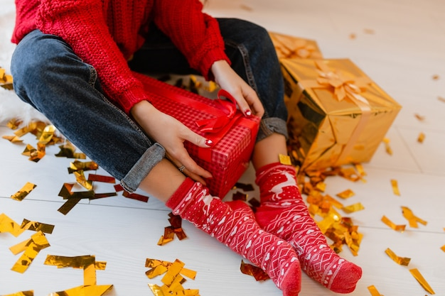 Vista de cima na mulher com meias vermelhas sentada em casa no natal com confetes dourados desempacotando peresents e caixas de presente