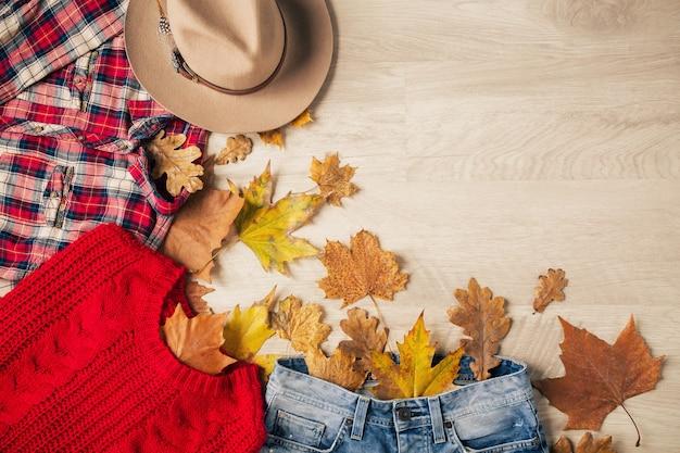 Vista de cima na postura plana de estilo feminino e acessórios, suéter de malha vermelho, camisa de flanela quadriculada, jeans, chapéu, tendência da moda outono, vista de cima, roupas, folhas amarelas
