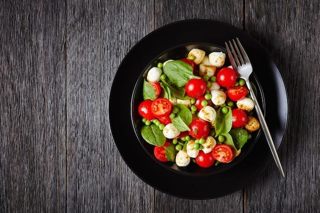 Vista de cima na salada caprese com espinafre baby, tomate cereja, mini queijo mussarela, vinagre balsâmico e molho de azeite em uma placa preta, em uma mesa de madeira, close-up, copie o espaço