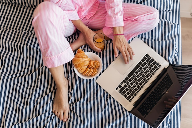 Vista de cima nas mãos de uma jovem de pijama rosa sentada na cama com um laptop tomando café da manhã
