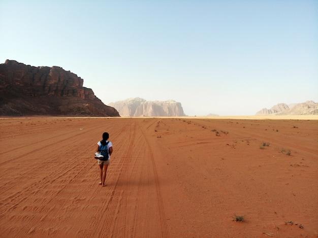 Vista de cima no enorme, vermelho, quente e muito deserto deserto wadi rum e young lady andando. reino da jordânia, país árabe na ásia ocidental