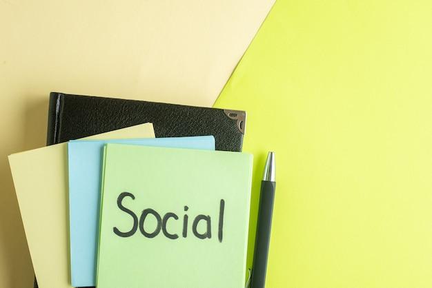 Vista de cima nota social escrita com adesivos e bloco de notas sobre fundo verde-amarelo faculdade trabalho escritório caderno escola salário dinheiro foto colorida