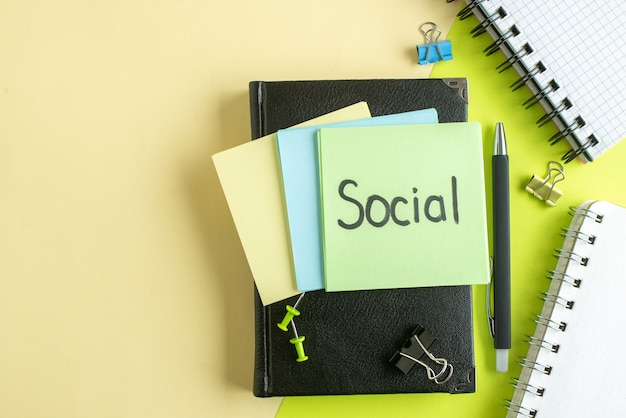 Vista de cima nota social escrita com adesivos e bloco de notas sobre fundo verde-amarelo faculdade trabalho escritório caderno salário dinheiro foto de negócios a cores