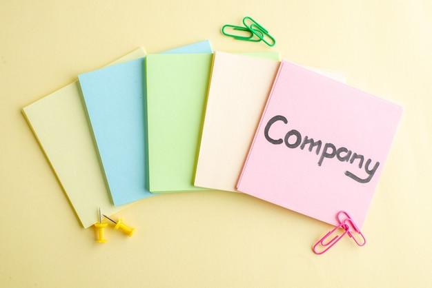 Vista de cima notas de papel coloridas com a escrita da empresa em uma delas na superfície clara trabalho de caderno banco escola de negócios bloco de notas caneta dinheiro trabalho